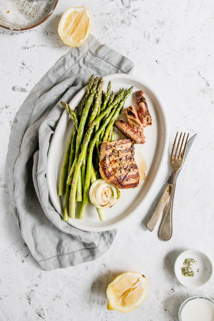 lamb steak with asparagus on a plate with ingredients on table