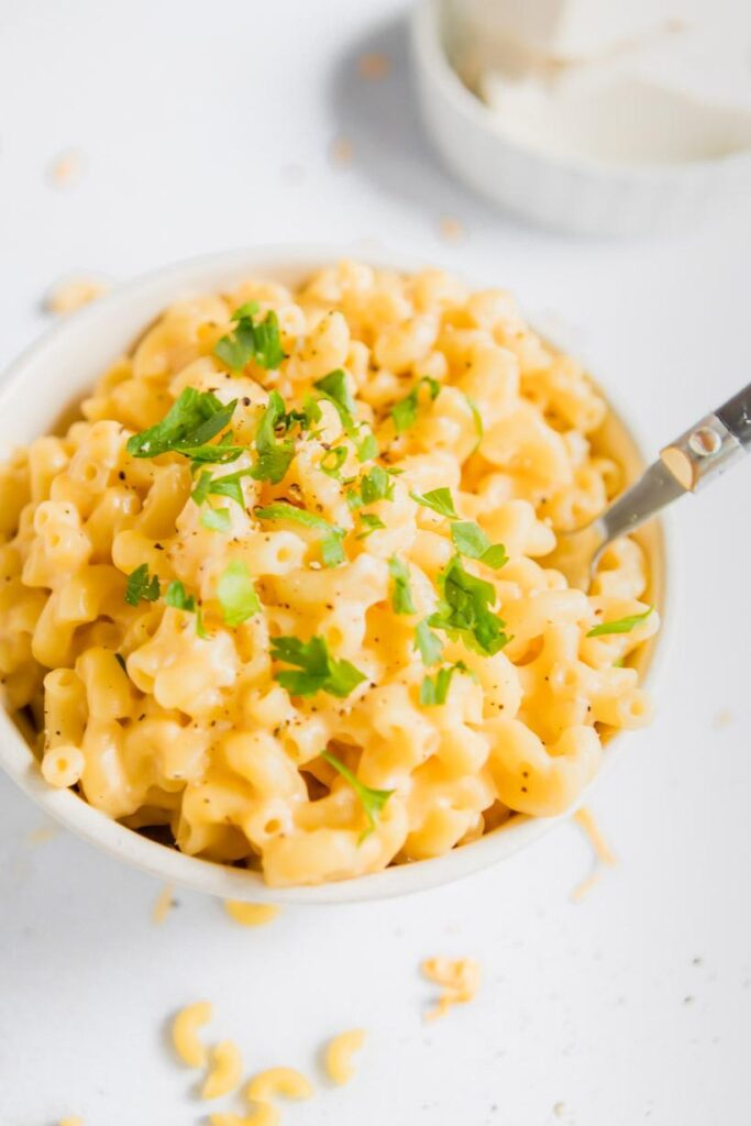 close up of mac and cheese in a bowl with parsley garnish