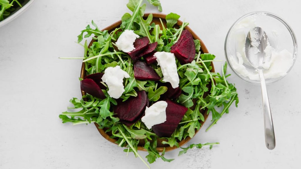 arugula, beets, and goat cheese for a beet and arugula salad on a plate