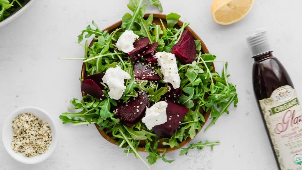 arugula, beets, goat cheese, and hemp hearts for a beet and arugula salad on a plate