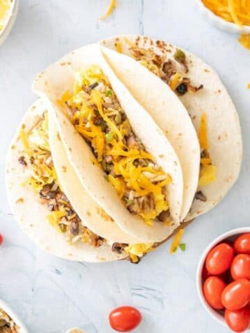 three open breakfast tacos with eggs and cheese surrounded by ingredients