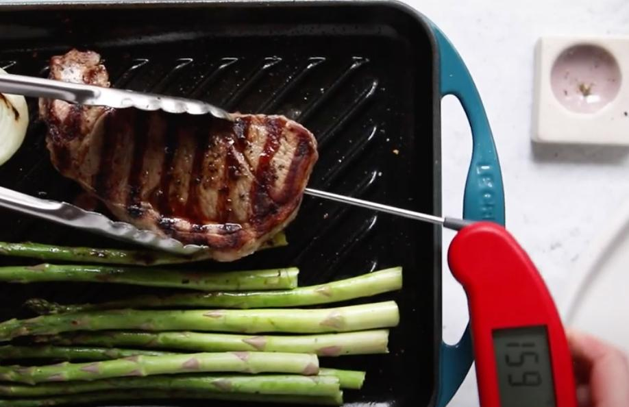 hand measuring temperature of lamb steak on a grill pan