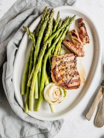 lamb steak and asparagus on a white oval plate