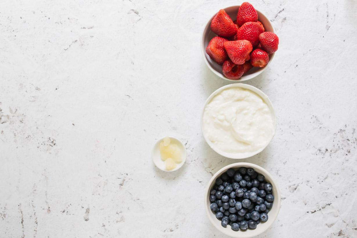 strawberries, yogurt, and blueberries in bowls on a table