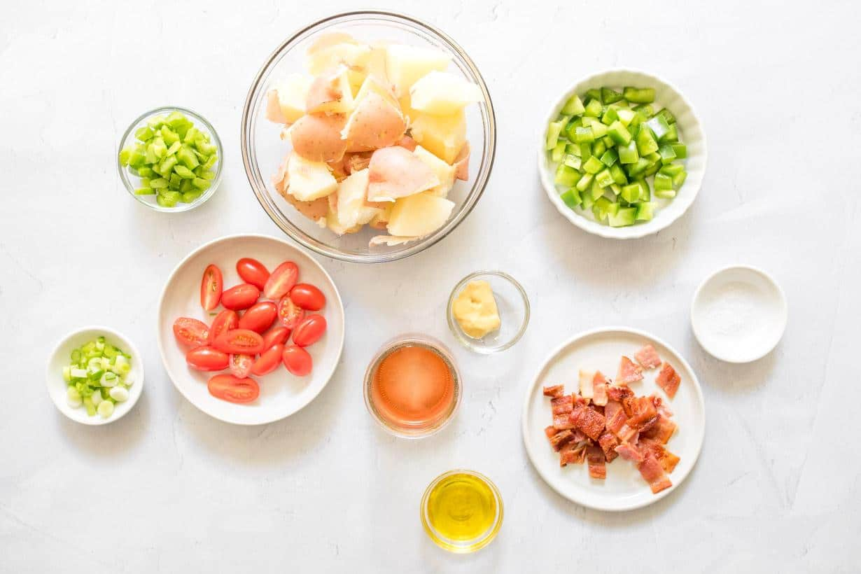 vegetables, cubed potatoes, bacon, and dressing ingredients on a table