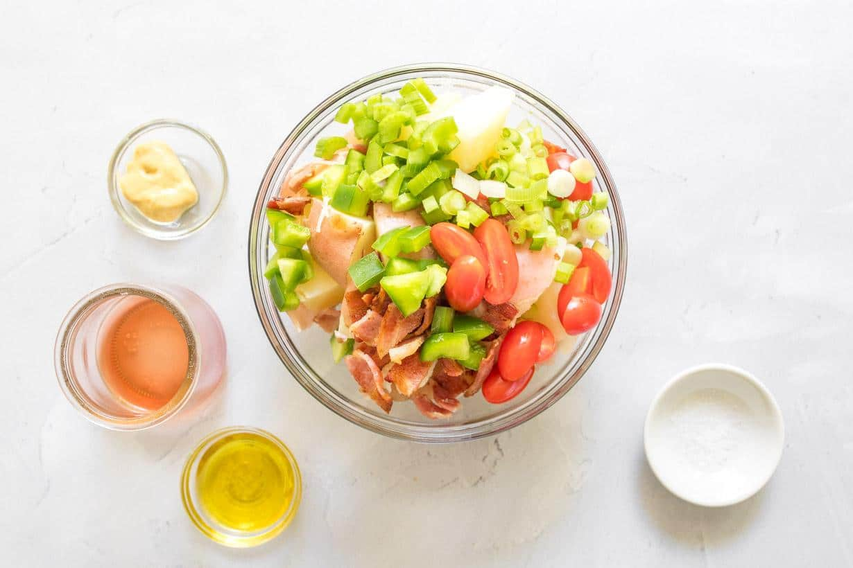 vegetable and potato salad with salad dressing ingredients on a table