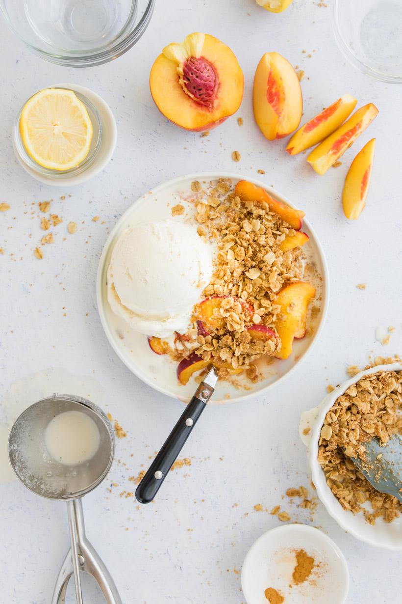 peach crumble in a bowl with ice cream and ingredients on a table
