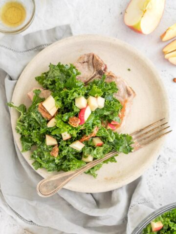 kale apple and pecan salad over a pork chop with ingredients on a table