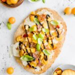 peach and prosciutto pizza caprese with ingredients on a table