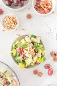 broccoli salad with grapes on a table with ingredients on table