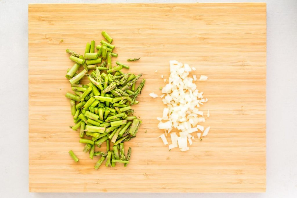 chopped asparagus and onions on a cutting board