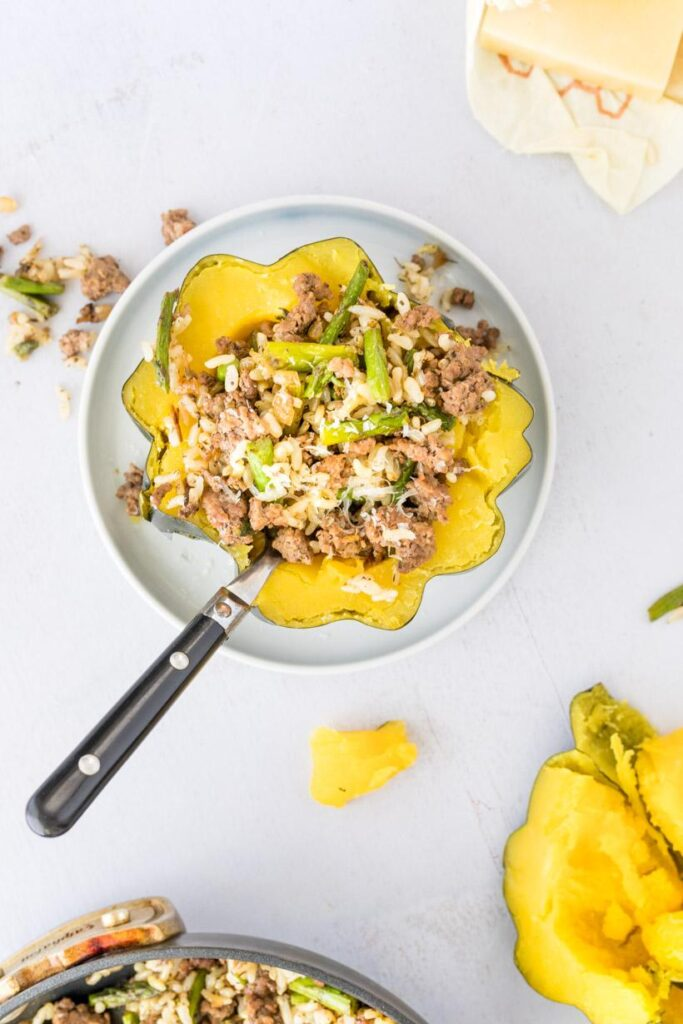 stuffed acorn squash recipe with ingredients on a table