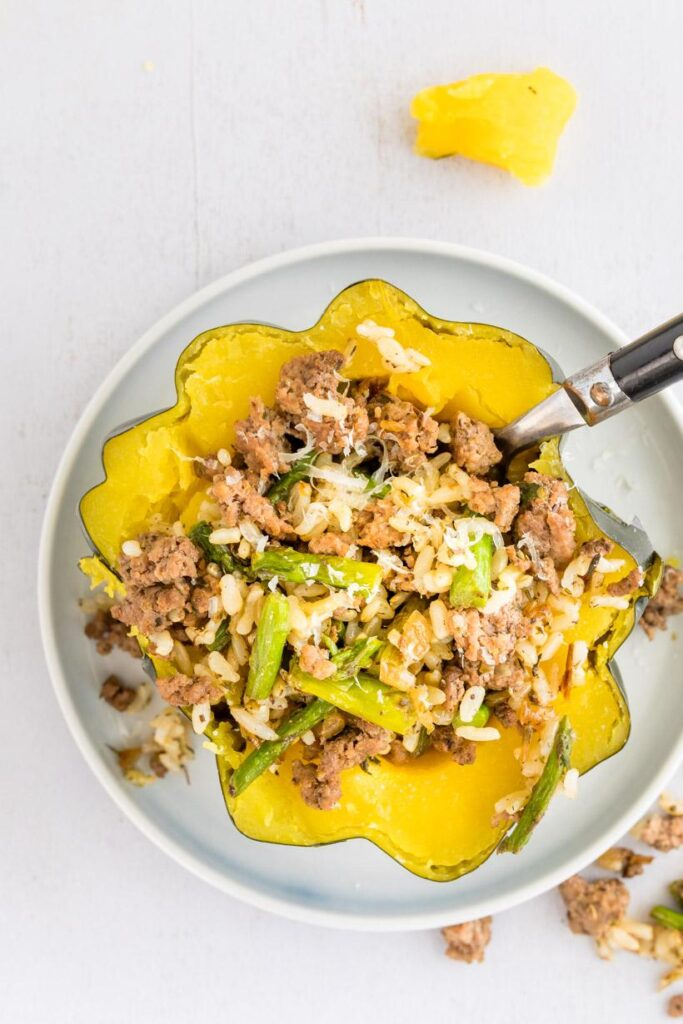 stuffed acorn squash recipe with a fork in it, on a plate