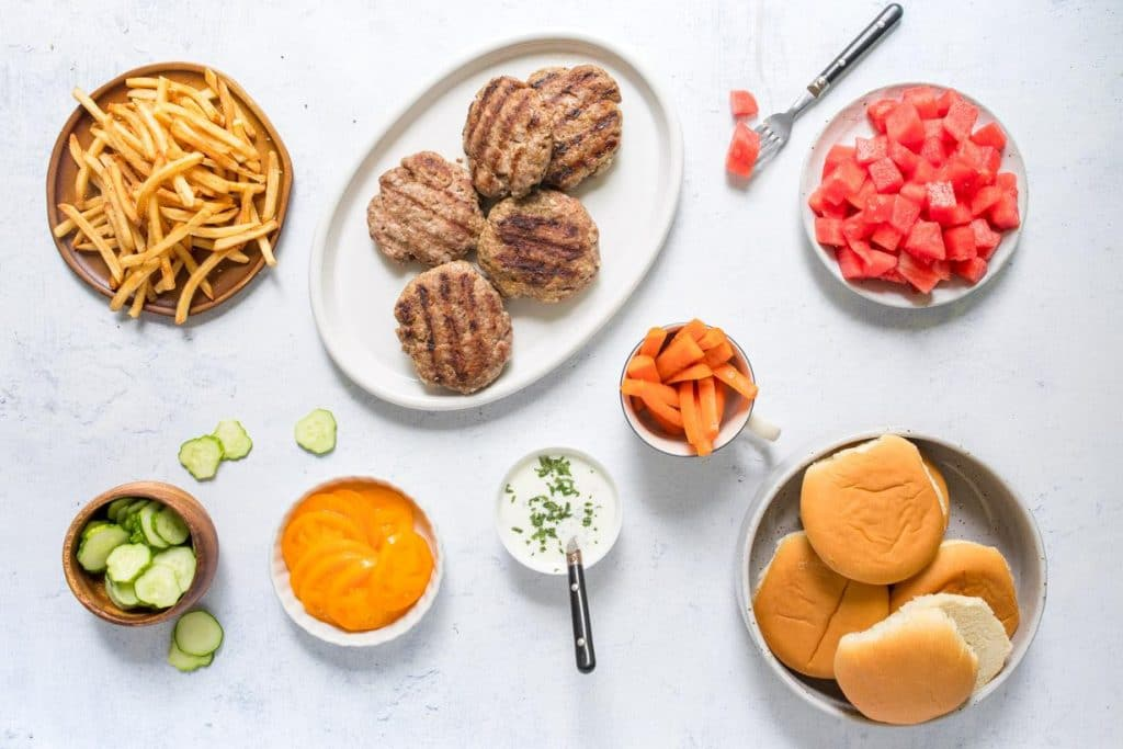 spiced lamb burgers and toppings on a table