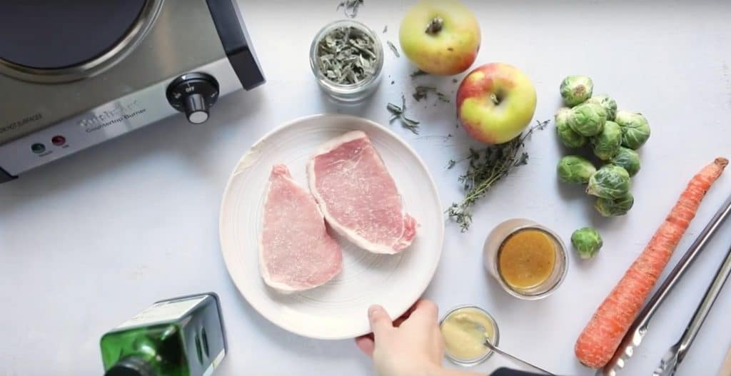 ingredients for pan fried pork chops with apples and vegetables on a table