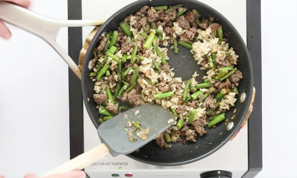 mixing ground beef, vegetables, and rice in sautee pan