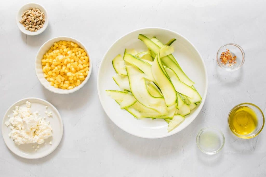 ingredients for zucchini salad with feta on a table