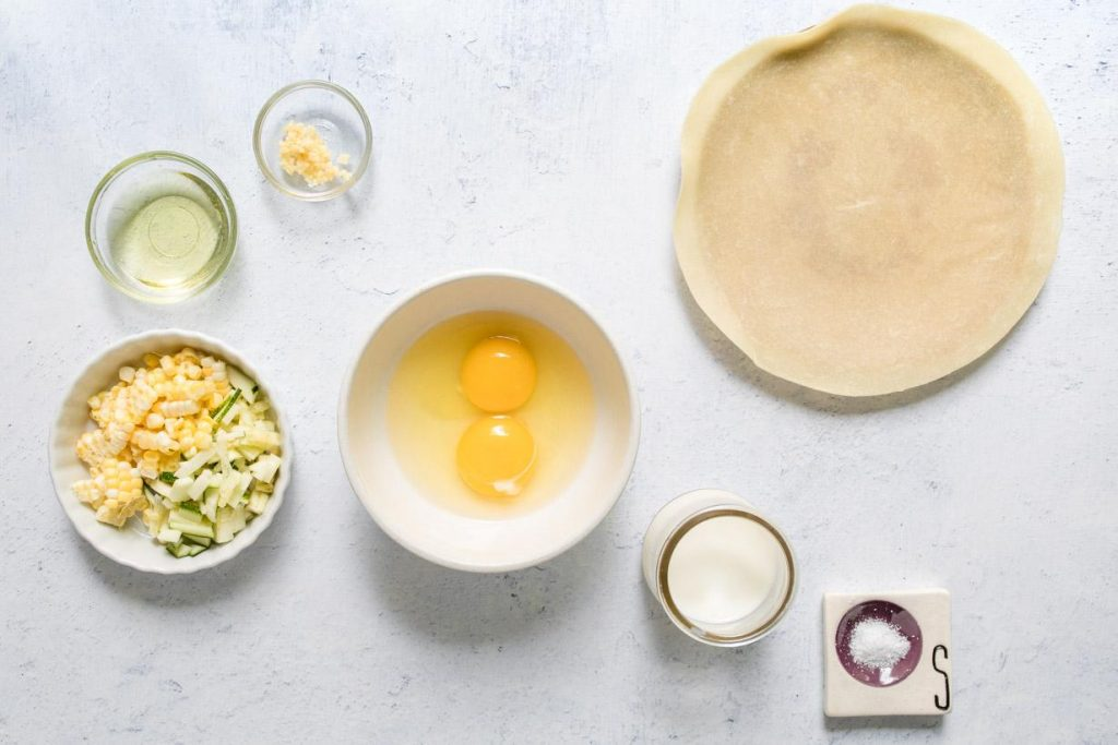 corn, zucchini, oil, garlic, two eggs, milk, an uncooked tortilla, and salt in bowls on a table