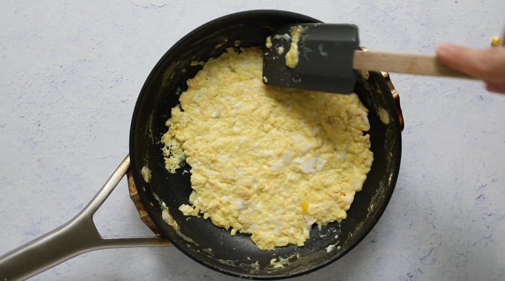 pressing down eggs with a spatula in a fry pan