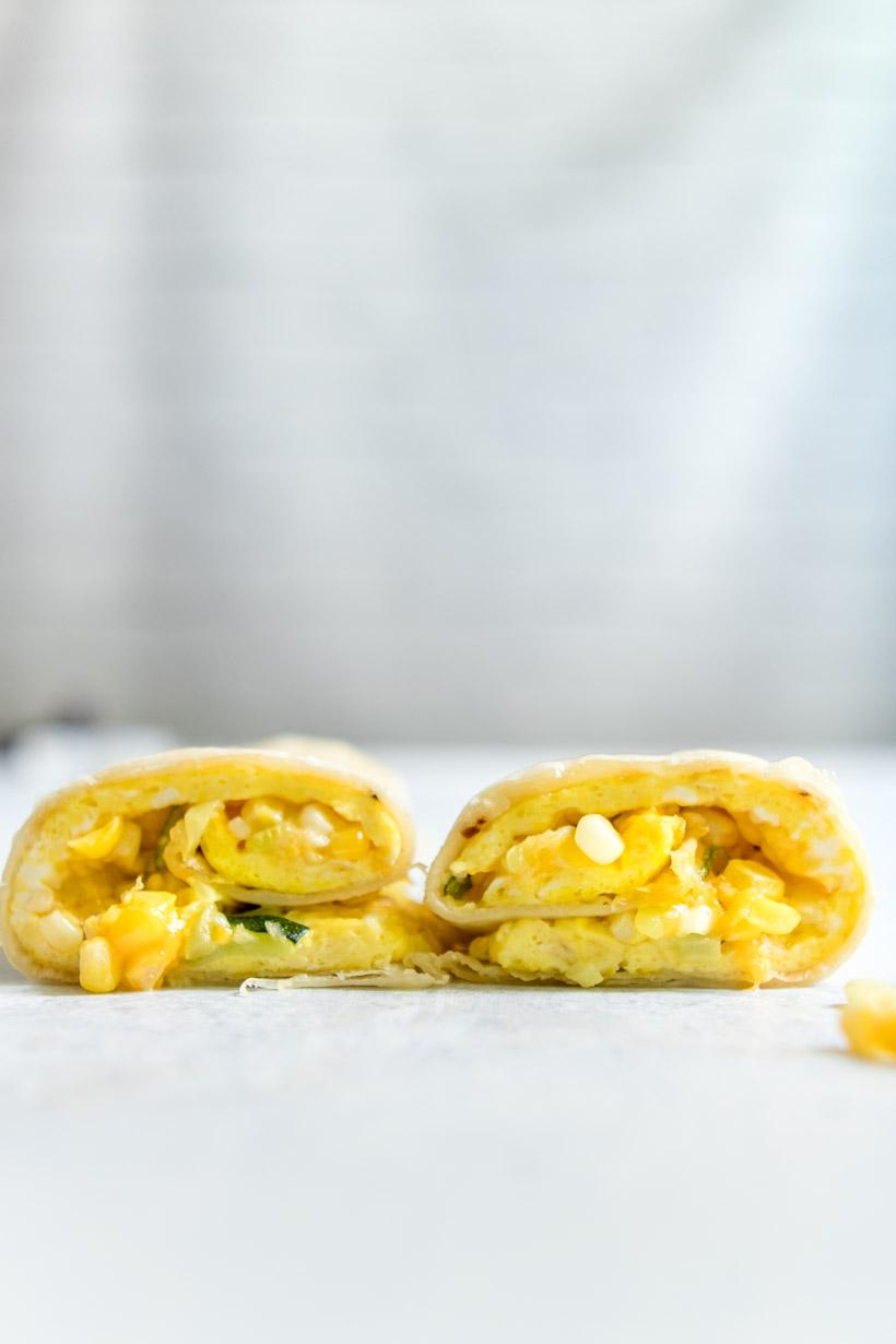 two halves of egg, vegetable, and cheese wrapped up in a tortilla