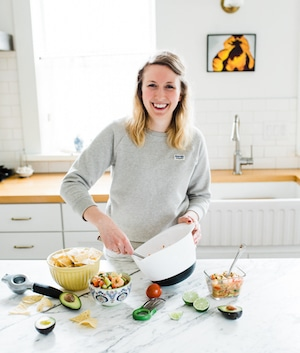 Rebecca of Nourish Nutrition Blog in a kitchen making guacamole with chips and dips on counter