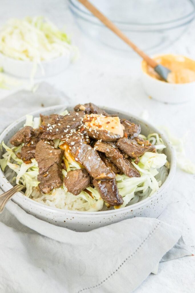 Korean bulgogi in a bowl with ingredients in background