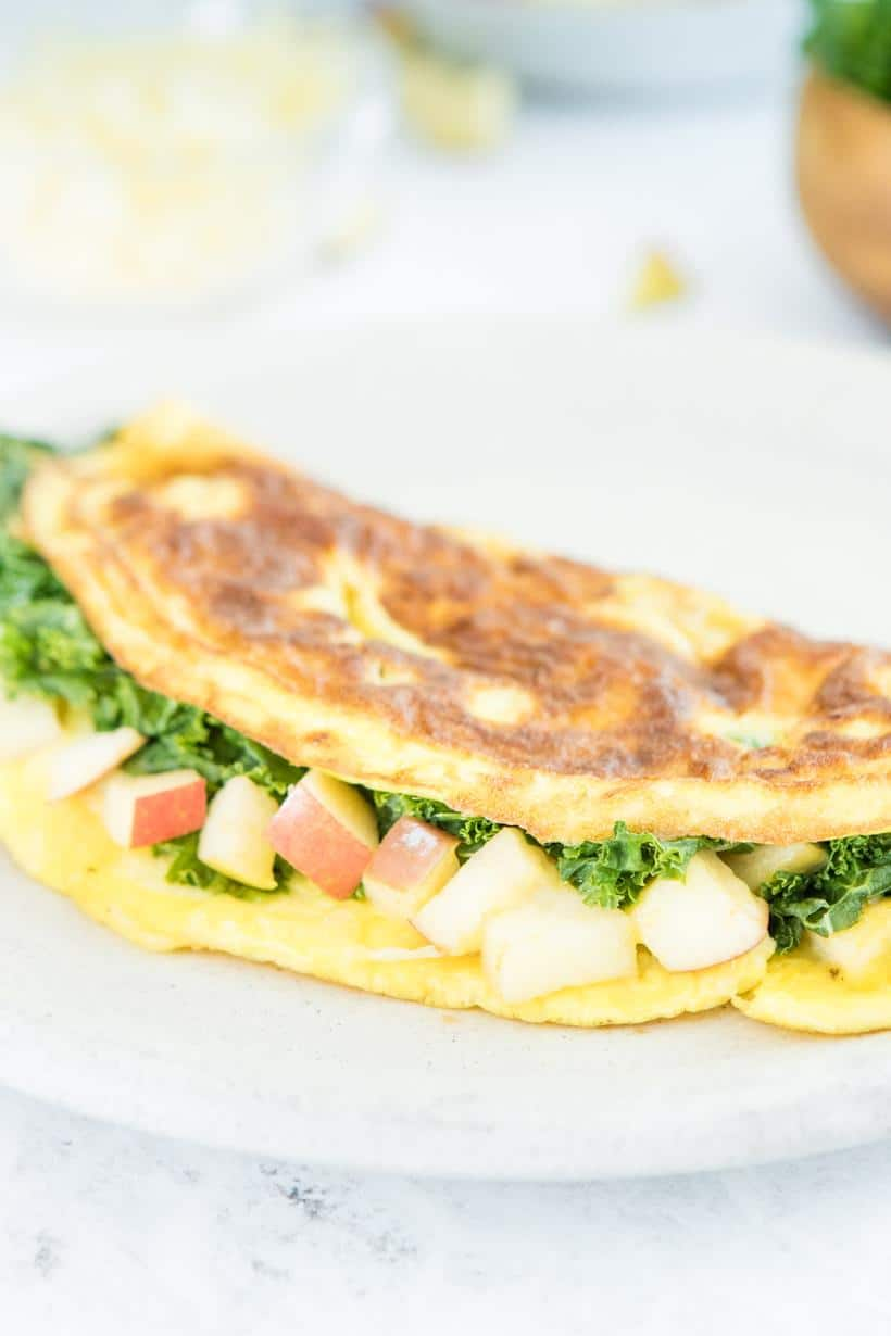 close up of an omelette with kale and apples on a plate