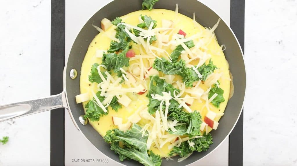 egg omelette in a pan with kale, apples, and cheese on top