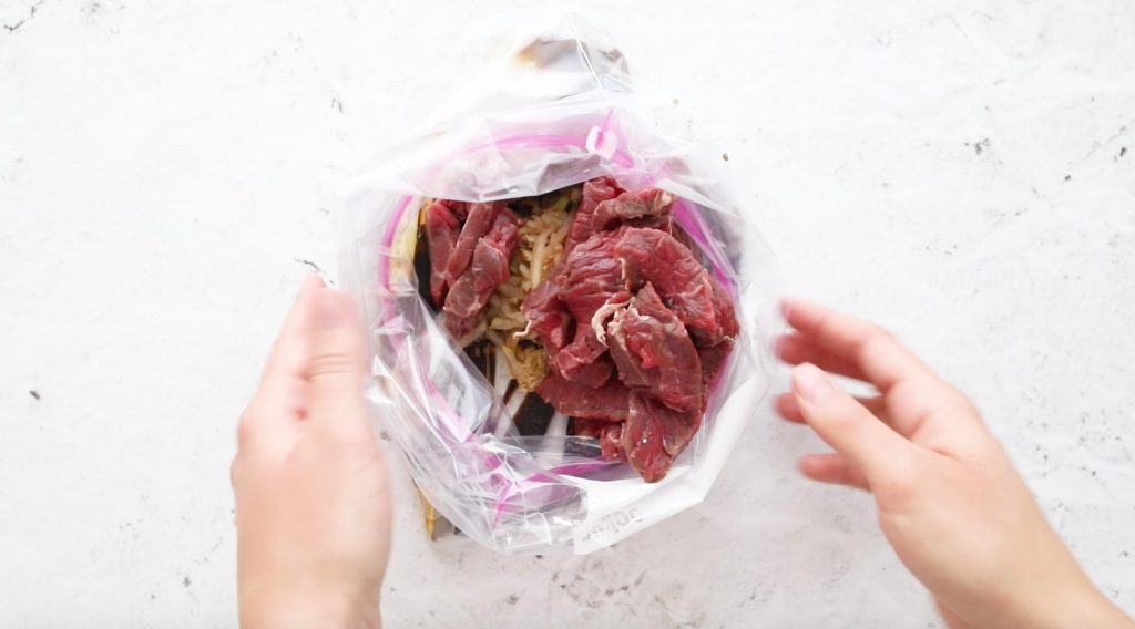 hands holding a plastic bag full of beef with marinade ingredients in it