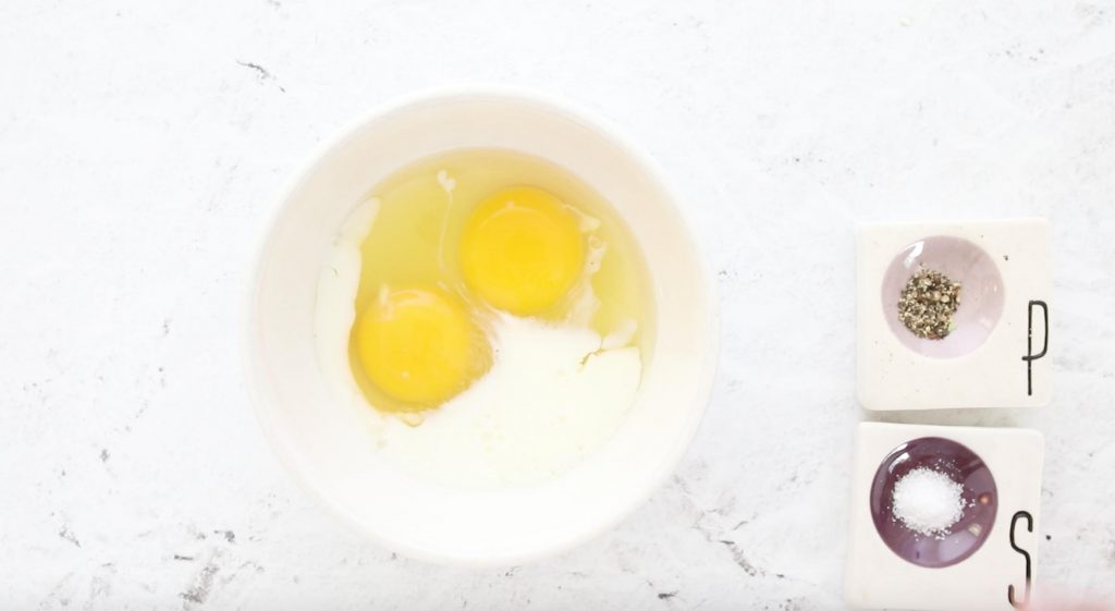 cracked eggs and milk in a bowl