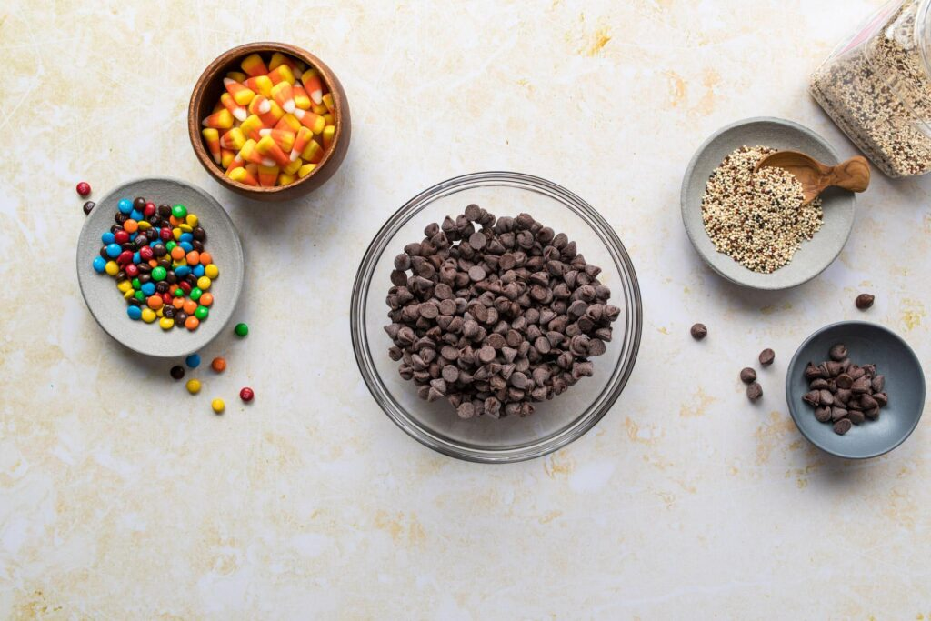 two hands holding chocolate chips in a glass bowl with candy on a table below