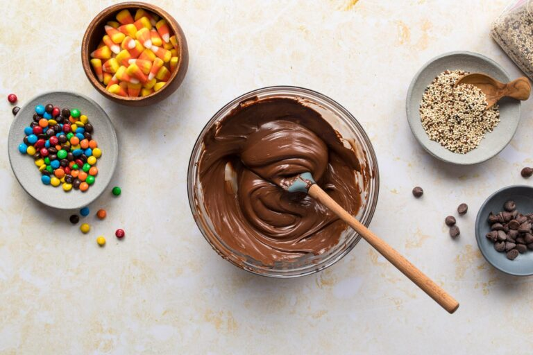 two hands holding melted chocolate in a glass bowl with candy on a table below