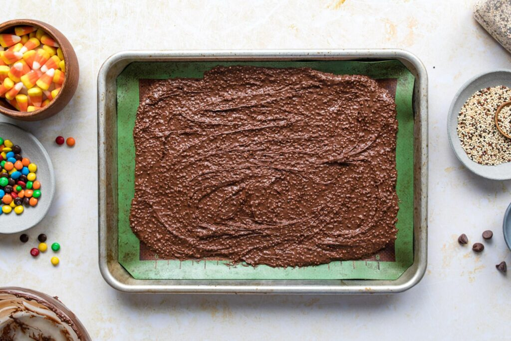 spreading melted chocolate onto a sheet pan