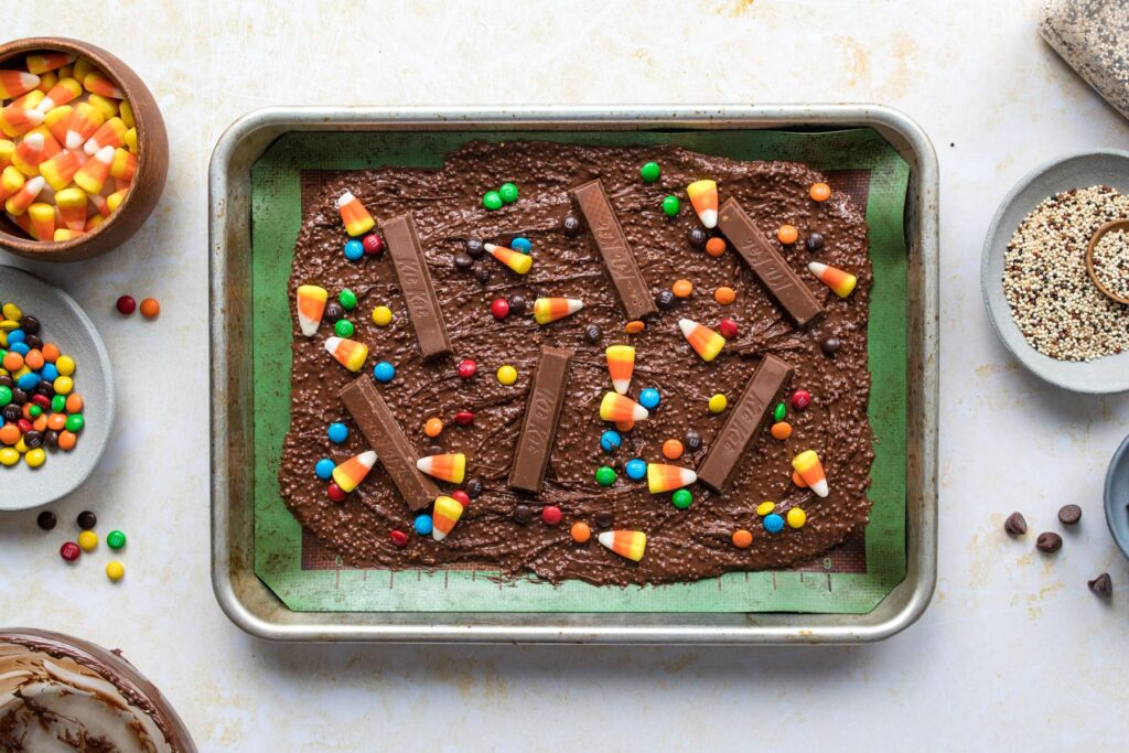sprinkling candy onto Halloween bark on a baking sheet