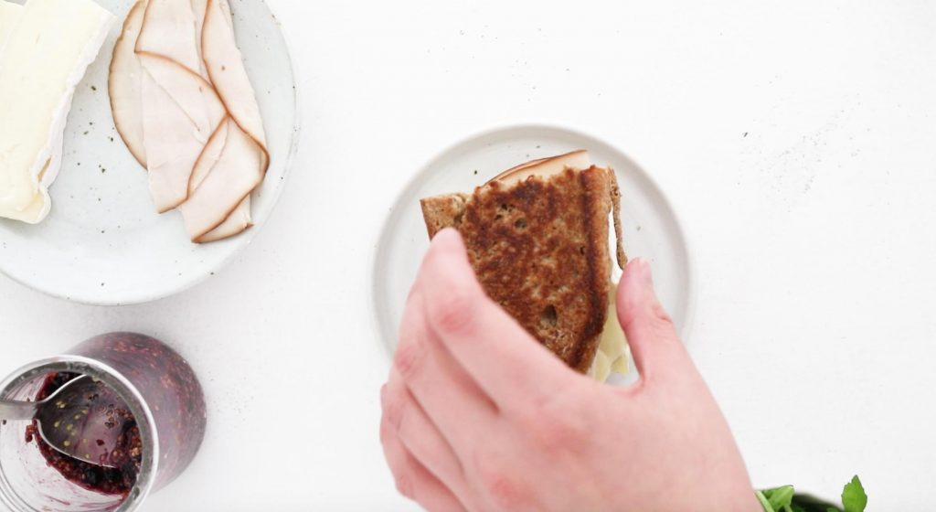 placing a slice of grilled bread on a sandwich
