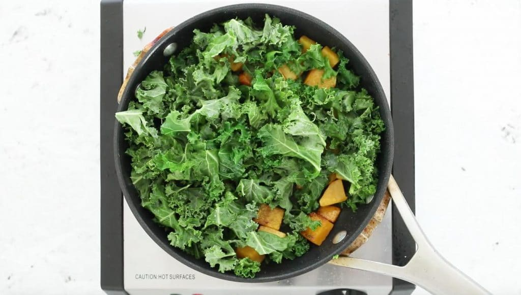 chopped kale and butternut squash in saucepan