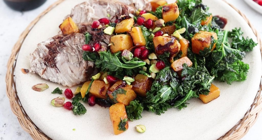 closeup of salad with kale, butternut squash, chopped pistachios, and pomegranate aerils with pork loin on a plate