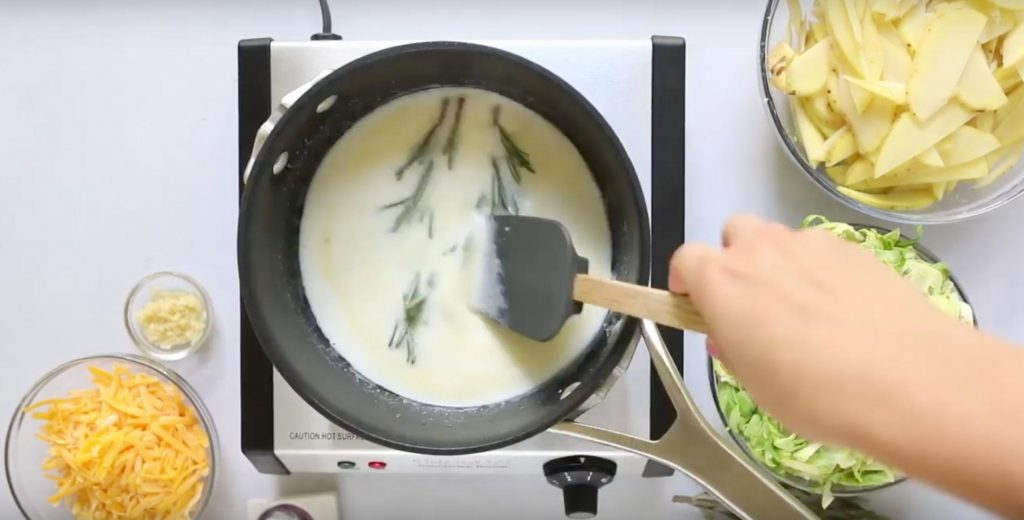 stirring two rosemary sprigs in a pot of milk