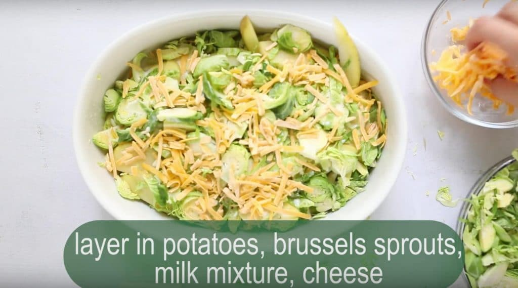 sliced potatoes, brussels sprouts, and cheese in a white baking dish with text overlay