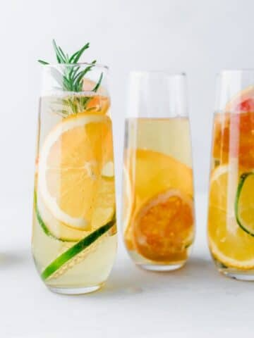 4 glasses of apple drink with citrus slices in it