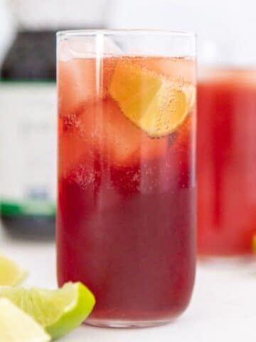 a tall glass of pomegranate juice with lime wedges in it and around it