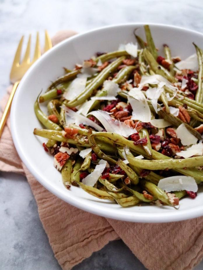 green beans with pecans, cranberries, and shaved parmesan cheese in a white bowl on a yellow towel