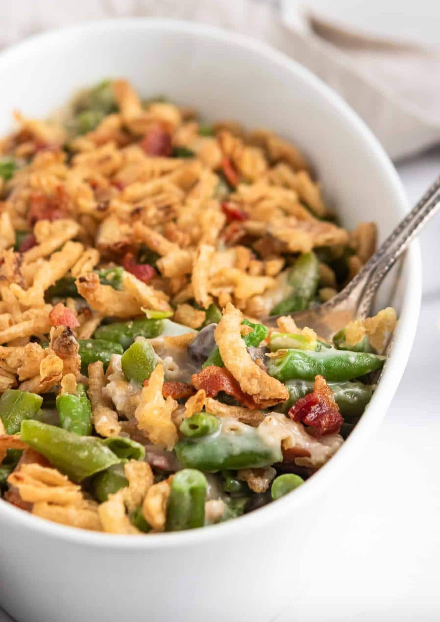 green bean casserole with bacon and fried onions in a white oval baking dish