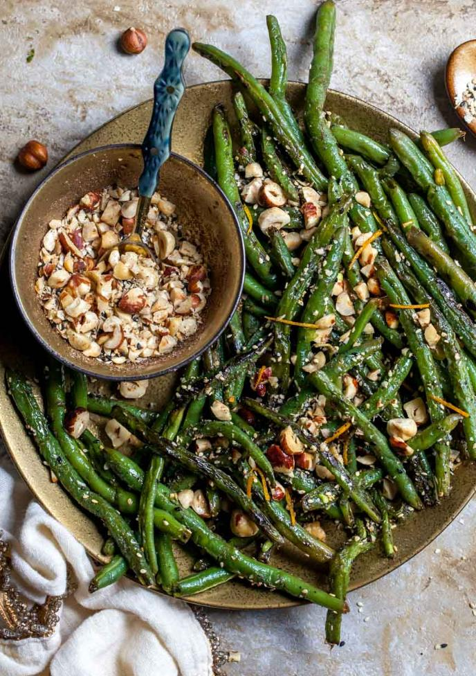 sauteed green beans with hazlenuts on top next to a bowl of chopped hazelnuts
