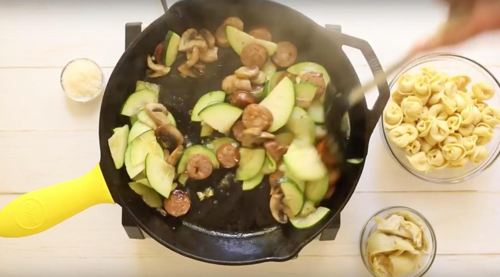 sliced sausage, mushrooms, and zucchini cooking in a cast iron skillet