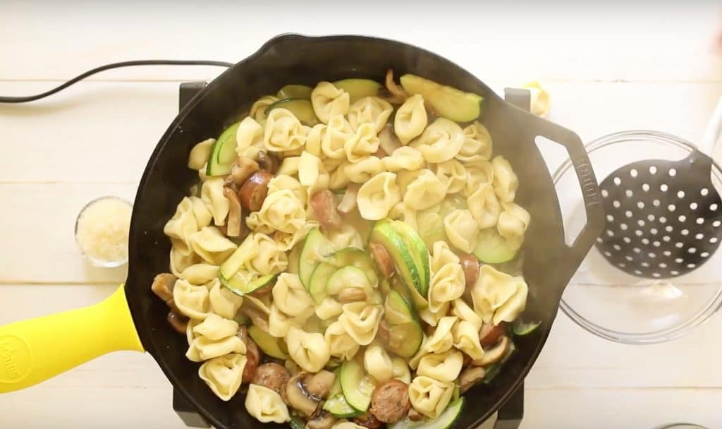 tortellini, zucchini, mushrooms, and sliced sausage cooking in cast iron skillet