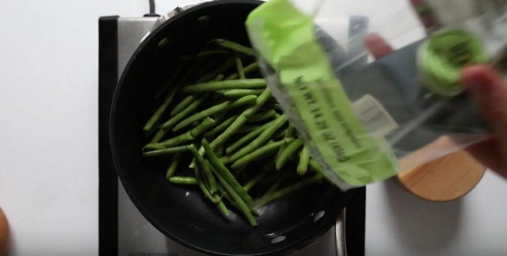 plastic bag pouring green beans into a black pot