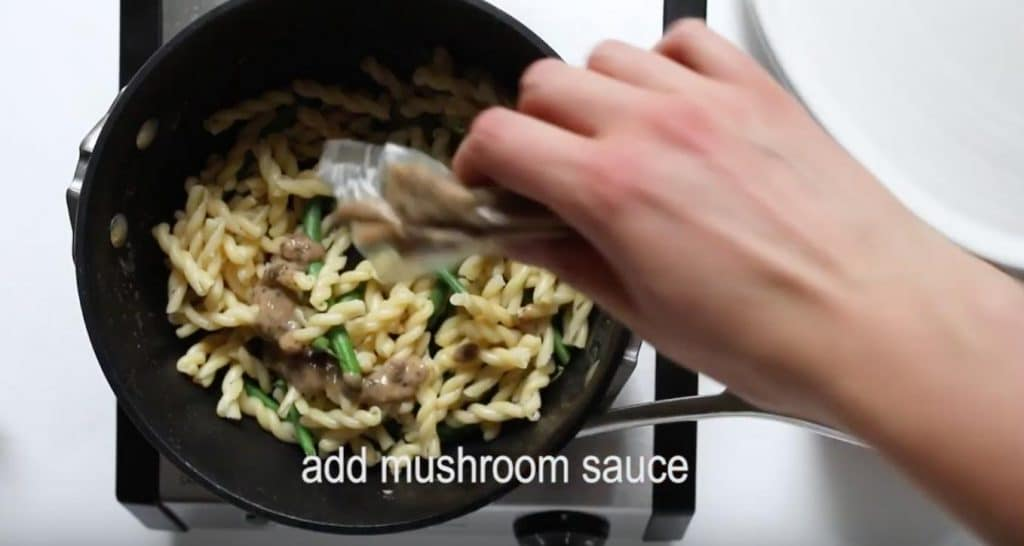 hand pouring mushroom sauce into a pot of pasta and green beans