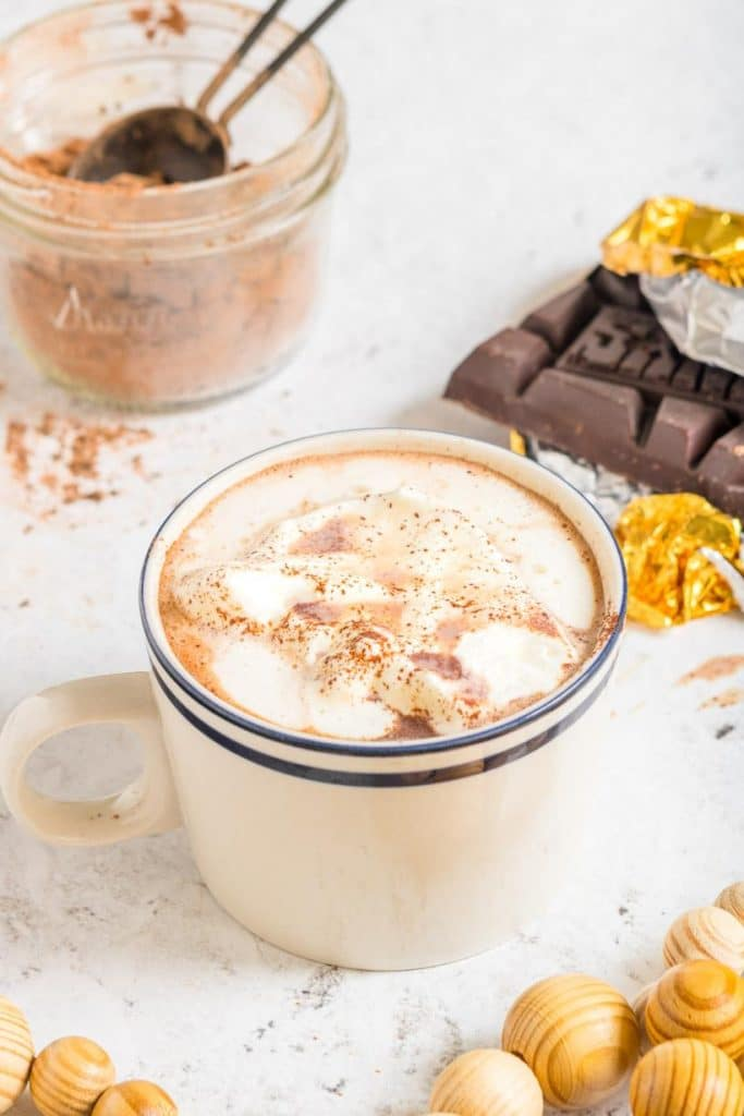 3 ingredient hot cocoa in a mug with ingredients surrounding it
