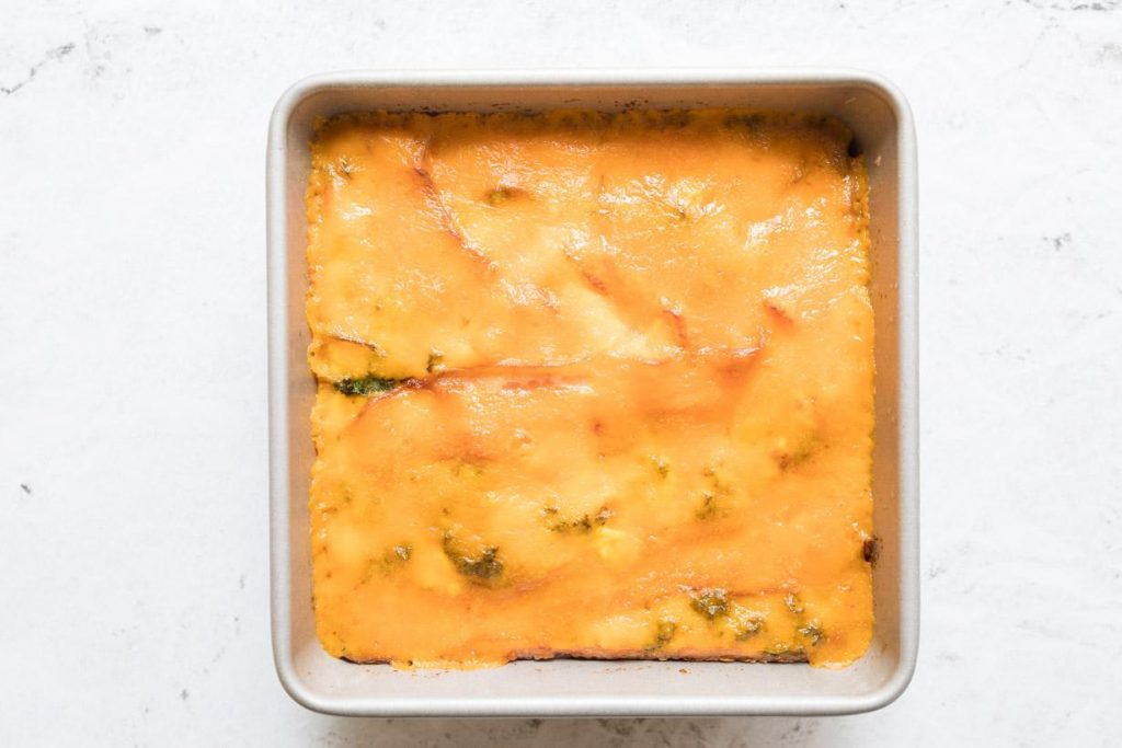 cooked eggs with cheese on top in a square baking pan